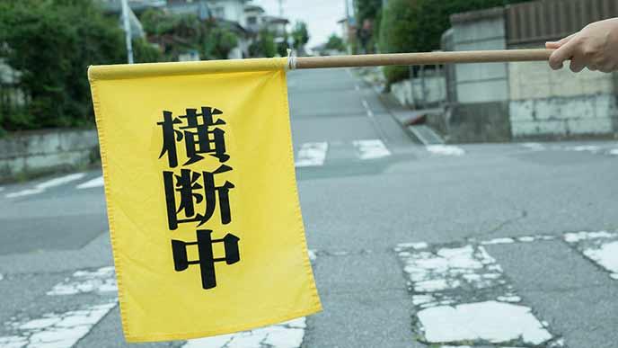 スクールガードが持つ横断中の黄色い旗
