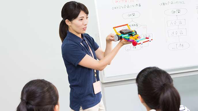 クラブ活動でロボット制作を教える女性