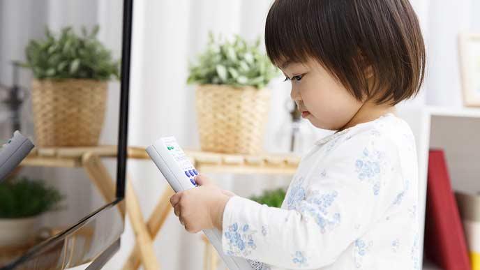 テレビのリモコンを持ってTVの前に立つ子供
