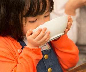 食事で汁ものを吸う女の子