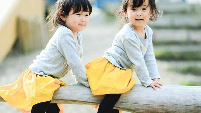 ペアの服装で遊ぶ双子の女の子